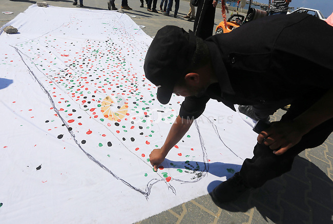 A Palestinian policeman paints his fingerprint on a large map of Palestine in an attempt to break a Guinness World Record by making the largest printed map of Palestine in Gaza city on June 14, 2015. Photo by Mohammed Asad