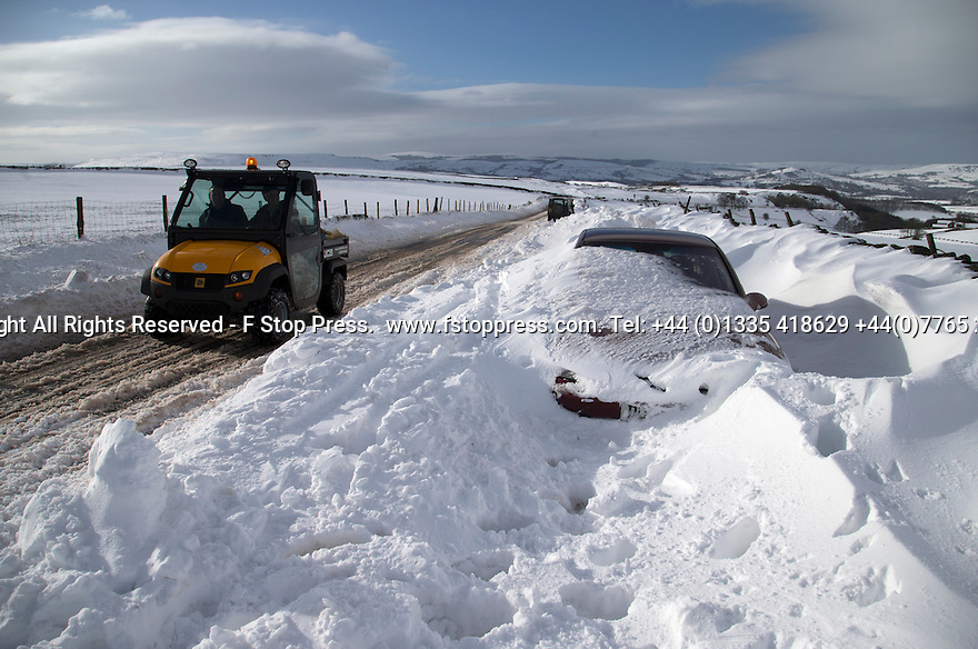 01/02/15<br /> <br /> After more overnight snow a farm vehicle full of animal feed passes a car buried in snowdrifts on Rushup Edge near Chapel-en-le-Frith in the Derbyshire Peak District.<br /> <br /> All Rights Reserved - F Stop Press.  www.fstoppress.com. Tel: +44 (0)1335 418629 +44(0)7765 242650