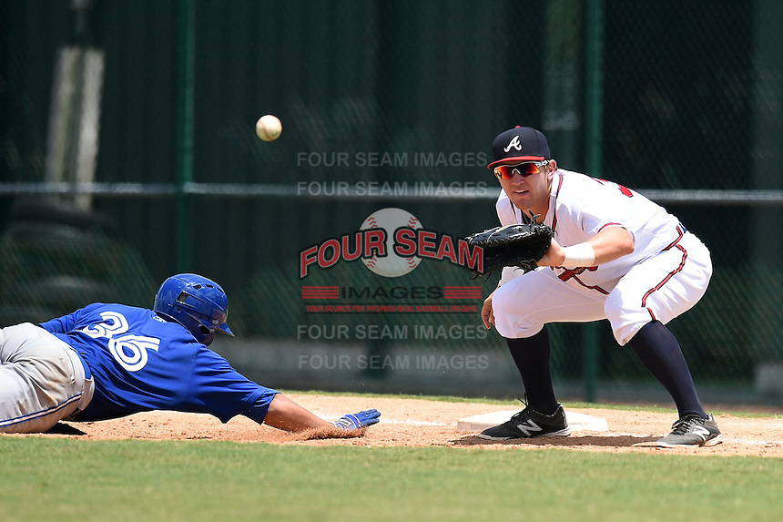 GCL Braves first baseman Ian Hagenmiller (32) takes a pickoff attempt throw as Matt Morgan (36) dives back to first during a game against the GCL Blue Jays on June 27, 2014 at the ESPN Wide World of Sports in Orlando, Florida.  GCL Braves defeated GCL Blue Jays 10-9.  (Mike Janes/Four Seam Images)