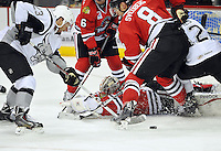 San Antonio Rampage right wing Jack Combs, left, fights for the puck against Rockford IceHogs goaltender Kent Simpson and Rockford defensemen Viktor Svedberg (8) and Jared Nightingale (6) during the second period of an AHL hockey game, Saturday, Oct. 5, 2013, in San Antonio. (Darren Abate/M3D14.com)