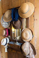 Straw hats and sunhats on hat stand in Hotel Corps de Garde, at St Martin de Re on Ile de Re, France