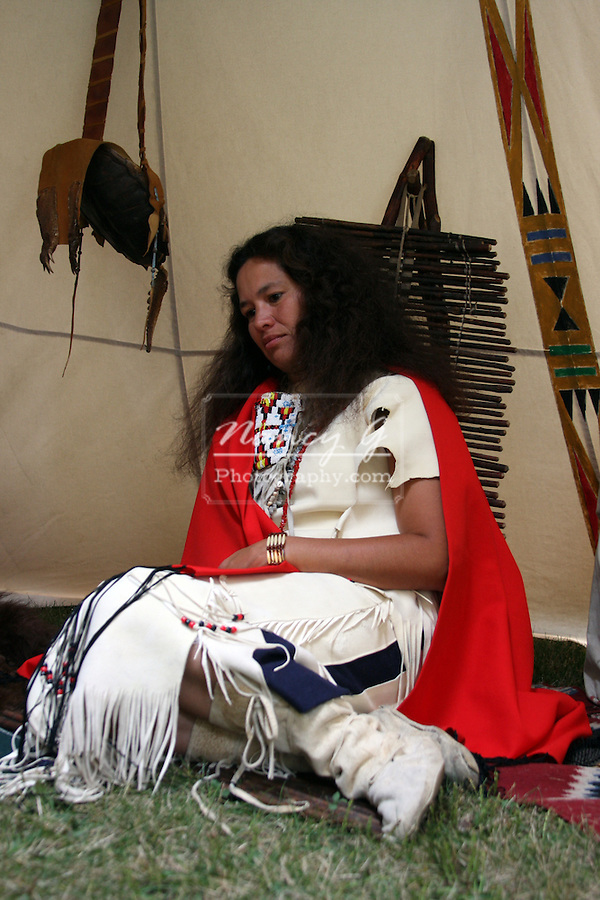 A Native American Lakota Sioux Indian woman resting in a tipi
