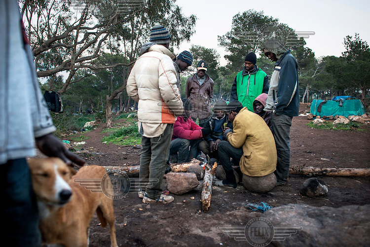 A group of migrants from Sub-Saharan Africa huddle around a fire trying to keep warm at their camp in the Gurugu Mountains. About 1200 migrants have set up a camp there deep in a forest, hidden from the police and authorities. It is is near the Spanish exclave of Melilla and many of the migrants try to break into the city in hope of eventually finding a way to enter Europe.