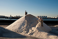 Allen Moon Partnership attempts to move a mountain of salt in his performance piece, representing a failed expression of masculinity, during the Lumen video and performance festival, held amidst piles of salt, used to prevent freezing on roads during winter storms, at Atlantic Salt Inc. in the New York borough of Staten Island on Saturday, June 23, 2012. The yearly free festival presents performance art and video in an industrial space on Staten Island. Because of an unusually mild winter Atlantic Salt has an over abundance in their inventory of salt creating a surreal landscape for the performers. (© Richard B. Levine)