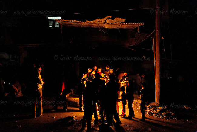 Children burn trash to provide heat next to the line of people waiting outside a bakery in the Shaar neighborhood of Aleppo. This fire is the only light that glow at night in this opposition neighborhood - electricity was cut ten days ago leaving people without the means to heat their homes as the temperatures drop in the early days of December.<br />