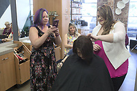 """NWA Democrat-Gazette/CHARLIE KAIJO Kasey Coonrod of Bentonville (right) works on the hair of Anna Sarratt as Rose Birdsong of Fayetteville takes a picture (left) during a formal hair class, Monday, May 13, 2019 at Sola Salons in Bentonville.<br /> <br /> """"A lot of stylists are new to this industry or want more confidence in this area and the best way is through education,"""" Kasey Coonrod said of her reason to have the class. """"Some stylists are intimidated by weddings and formal events."""""""