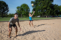 Fit attractive female athlete serves the ball during a volleyball match at Zilker Park, Austin, Texas. Volleyball is a favorite summer fitness activity for active fitness crazed Austinites.