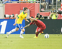 Brazil defender Maxwell (14) avoids a tackle by Portugal midfielder Vieirinha (11).  In an International friendly match Brazil defeated Portugal, 3-1, at Gillette Stadium on Sep 10, 2013.