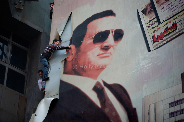 Protesters remove a large poster of Egyptian President Hosni Mubarak from a building on Ramsis Street, Cairo, Egypt, Friday, Jan. 28, 2011. Tens of thousands of people took to the streets after Friday prayers, demanding that Mubarak step down. Demonstrators clashed with police throughout the day and night as they marched toward Tahrir Square.