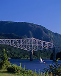 Sailboat on the Columbia River late afternoon going under The Bridge of the Gods that connect the Oregon side with the Washington side Cascade Locks Oregon State USA