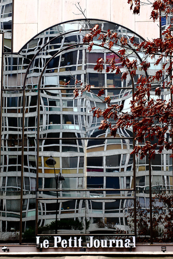 In Paris near Montparnasse , the beautiful mirror glass wall of a building, which overheads an old banner (Le Petit Journal – The Small Newspaper), with  the strange prospective of the reflected image of the building in the other side of the road, a street lamp, and a tree with dry red leaves. Digitally Improved Photo.