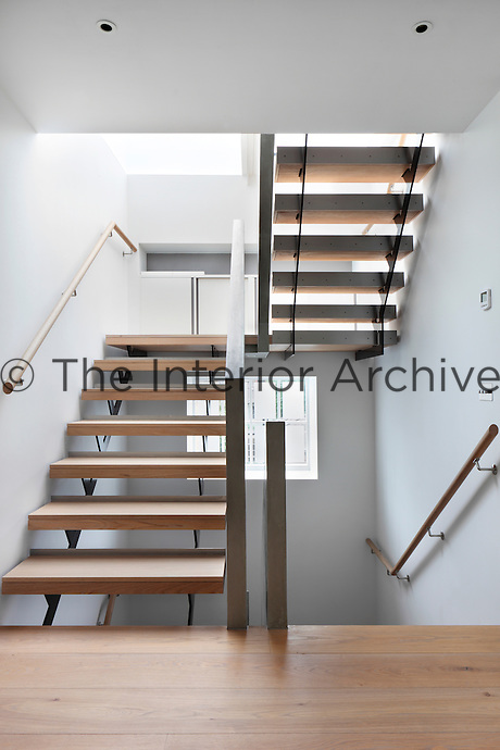 A hallway with a modern staircase with wooden treads.