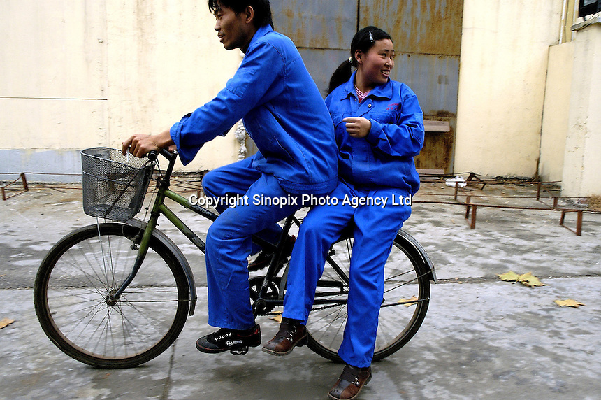 Female worker hitches a ride on back of colleague's bicycle at lunch break at a wood floor factory, a private firm which produceing floor boards for the booming domestic market and for export to Europe (including UK) and the United States, using wood imported from Asia and South America.