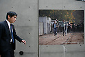 Nov 10, 2009 - Tokyo, Japan - A Japanese businessman walks past large pictures depicting the collapse of the Berlin Wall along the wall of the German Embassy in Tokyo.