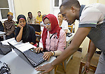 Refugee women and men in a computing class in a school operated by St. Andrew's Refugee Services in Cairo, Egypt. The school is supported by Church World Service.