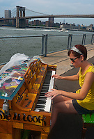 "New York, NY -  26 June 2010 Woman plkaying a piano in Brooklyn Brodge Park..Play Me I'm Yours"" is a musical installation by British artist Luke Jerram who has been touring the project globally since 2008. From 9am-10pm each day, 60 pianos will be available to play across New York City. Presented by Sing for Hope they are located in public parks, streets and plazas the pianos will be available until 5th July for any member of the public to play and engage with."