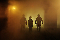 Three firefighters walk out of a smoke filled building.  Smoke training inside the fire house of the Occidental Volunteer Fire Department using a smoke machine with all of the fire engines removed.