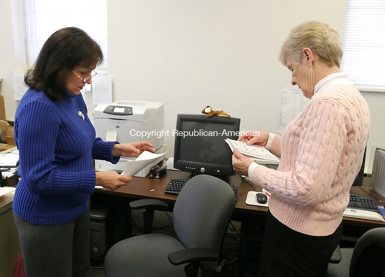 SOUTHBURY, CT 01/14/08- 011408BZ03- Lynn Dwyer, deputy town clerk, left, and Fay DeForest, deputy registrar of voters (D), look over forms submitted for absentee ballots from Germany and Massachusetts at Southbury Town Hall Monday morning.<br /> Jamison C. Bazinet Republican-American