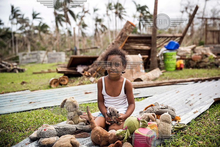Five year old Paloma with a few soft toys collected from the remains of St Martin's kindergarten which was destroyed by Cyclone Pam on 13 March 2015.
