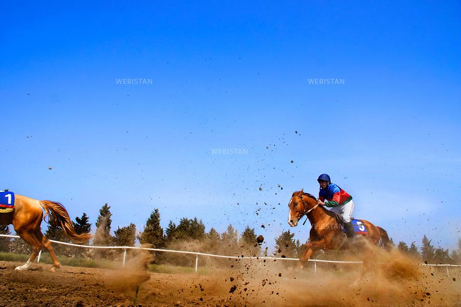 Azerbaijan, Absheron Peninsula, Bine, Hippodrome, April 15, 2012<br /> A man races on a Karabakh horse. These fabled and rare horses play a major cultural role in Azerbaijan. They are named after the geographical region where they were bred and are known for their compact bodies, strength, speed and endurance.<br /> <br /> Azerba&iuml;djan, p&eacute;ninsule d'Abcheron, Bina, hippodrome, 15 avril 2012<br /> Un homme sur un des chevaux l&eacute;gendaires et rares du Karabakh, qui ont une grande importance dans la culture azerba&iuml;djanaise. On leur donne le nom de la r&eacute;gion o&ugrave; ils ont &eacute;t&eacute; &eacute;lev&eacute;s et sont connus pour leur corps athl&eacute;tique, leur force, leur vitesse et leur endurance.