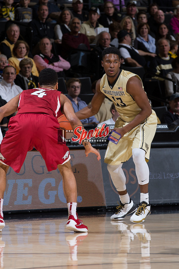 Bryant Crawford (13) of the Wake Forest Demon Deacons is guarded by Jabril Durham (4) of the Arkansas Razorbacks during first half action at the LJVM Coliseum on December 4, 2015 in Winston-Salem, North Carolina.  The Demon Deacons defeated the Razorbacks 88-85.  (Brian Westerholt/Sports On Film)