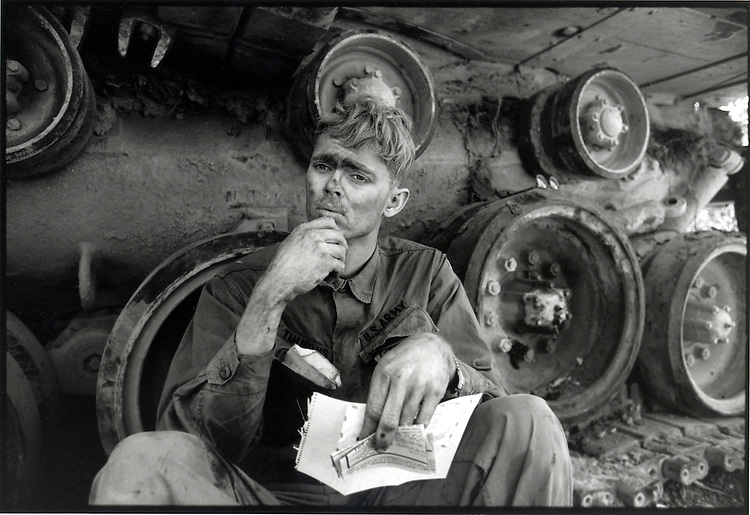 An American soldier reads a letter from home, while taking a break from repairing a tank tread. Lang Vei, March 1971
