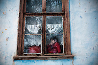A child looks from the window of their home in Min Kush.