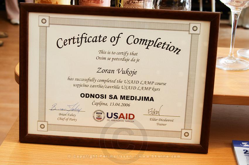 Diploma certificate showing that the owner Zoran Vukoje has successfully completed the USAid course., in the winery tasting room. Vukoje winery, Trebinje. Republika Srpska. Bosnia Herzegovina, Europe.