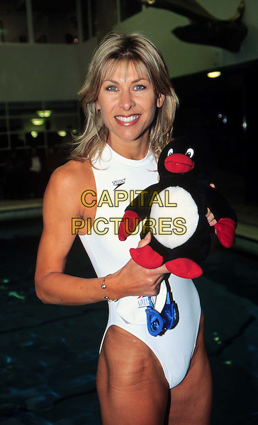 SHARRON DAVIES.Ref: 10317.swimsuit, toy penguin, half length, half-length white.*RAW SCAN - photo will be adjusted for publication*.www.capitalpictures.com.sales@capitalpictures.com.© Capital Pictures