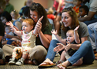 NWA Democrat-Gazette/ANDY SHUPE<br /> Kayla Mayer (left) and her daughter, Coraline Mayer, 19 months, sing alongside Eva Terry and her daughter, Fiona, 14 months, all of Fayetteville, Saturday, July 7, 2018, while enjoying traditional songs performed by Sarina Montgomery and Kenderick Scorza of Bright Star Theatre during Super Saturday at the Fayetteville Public Library.