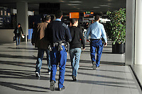 Immigrants are taken in by Dutch border police at Schiphol Airport after they travelled from Greece to the Netherlands.