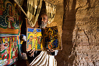 The priest of Mikael Melehayzenghi rock hewn church shows his colourful Ge'ez bible.