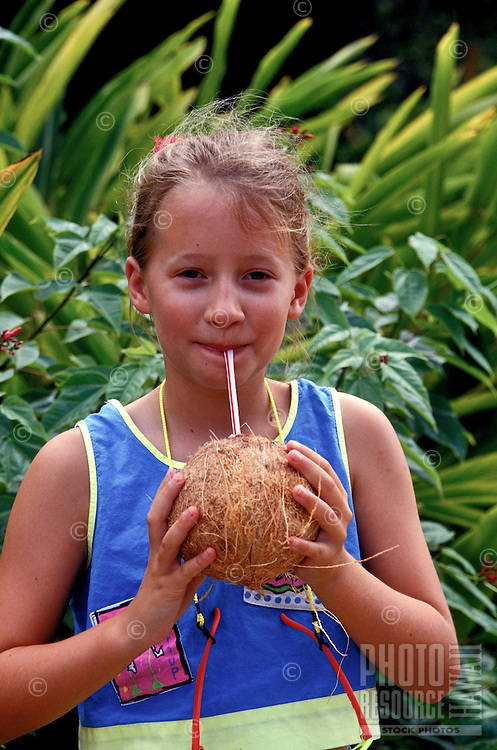 A young girl standing in front of green foliage smiles as she sips juice from a straw poked in a fresh coconut.