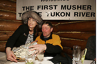 Brooke McGrath presents Paul Gebhart with his $3500 cash prize after Paul enjoyed his 7-course meal by the Millenium hotel in Ruby for being the first musher to the Yukon River.