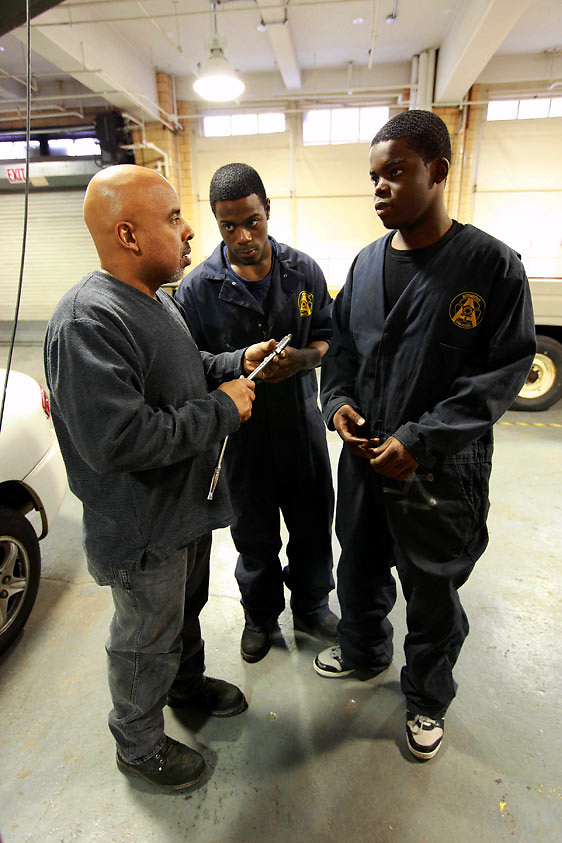 Automotive HS, Brooklyn, NY on Friday, January 22, 2010.  High school students have the opportunity to participate in a special program where they perform basic maintenance and repairs on privately owned cars at very competitive prices.  Students Joshua Smalls, 17, center, and Harry Cange, 17, right, listen intently to their teacher Carlos Caraballo.