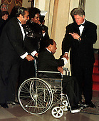 United States President Bill Clinton welcomes Lionel Hampton to the White House Dinner in honor of the recipients of the National Medal of Arts in Washington, D.C. on January 9, 1997.  U.S. Representative Charles Rangel (Democrat of New York) pushes Mr. Hampton's wheelchair..Credit: Ron Sachs / CNP