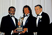 Chicago Bears running back Walter Payton (34), left, and American actor, director, screenwriter, and producer Sylvester Stallone, center, hold the Timmie Award, hold the trophy to be presented to defensive tackle Chad Hennings of the United States Air Force Academy, the 1987 College Lineman of the Year.  The award is presented in the memory of Knute Rockne by the Washington, DC Touchdown Club in Washington, DC on January 23, 1988.  At right is former Washington Redskins head coach George Allen.<br /> Credit: Arnie Sachs / CNP