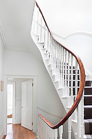A traditional elegant staircase with wooden banister and painted spindles in a white hallway.