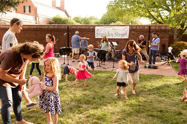 May 8, 2015. Chapel Hill, North Carolina.<br />  Barbie McGarrah and her 2 year old daughter Cassidy (at right) dance to the Franklin Street band on the lawn of the Carolina Inn.. <br />  On Friday nights between April 24th and October 23rd, the historic Carolina Inn hosts Fridays on the Front Porch with local music, food trucks and drinks on the large front lawn.<br />  Outsiders tend to lump Chapel Hill with nearby Durham, but the more sensible pairing is with Carrboro, the adjacent town that was once a mere offshoot known as West End. Even today the transition from Chapel Hill, anchored by North Carolina''s flagship public university, into downtown Carrboro is virtually seamless.