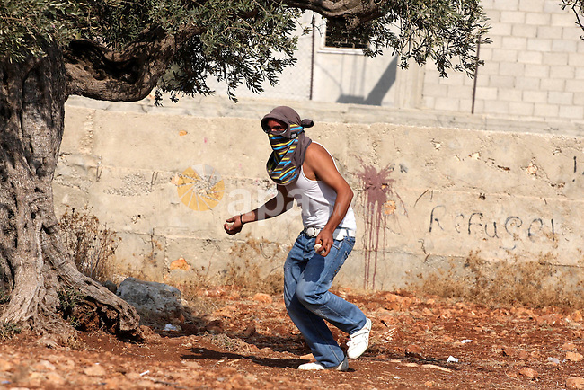 A Palestinian youth hurls stones towards Israeli soldiers during a protest against Israel's separation barrier as masked Palestinian stones throwers clash with Israeli soldiers in the West Bank village of Bilin, near Ramallah, on November 12, 2010. Clashes erupted during the weekly demonstrations, which are aimed at halting the construction of Israel's controversial separation barrier that is mostly built inside the occupied territory and cuts off farmers from their land in border communities like Nilin. Photo by Issam Rimawi