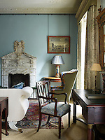 The sitting room is decorated in a cool blue with traditional furnishings and the George I marble chimneypiece provides an impressive focal point.