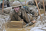 Michael Lawson of the 21st Co. crawls through a muddy trench while carrying a rifle and pushing an ammo can at the 2010 Sea Trials at the Naval Academy.