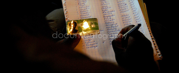A list of names is written on a piece of papers. those names are the list of the ones who don't have official papers to stay in France. A group of volunteer decided to record them in order to give the list to the officials who can arrange their situation.