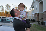Justin Griffith, a sergeant in the US Army, an atheist and a father, kisses his 1-year-old daughter Zoe Griffith at home in Fayetteville, NC, on Sunday, March 11, 2012.  Recently named as Military Director of American Atheists, Justin Griffith is trying to get atheists more respect within the military and has organized a pro-atheism event, Rock Beyond Belief, at Fort Bragg, where he is stationed.  Photo by Ted Richardson