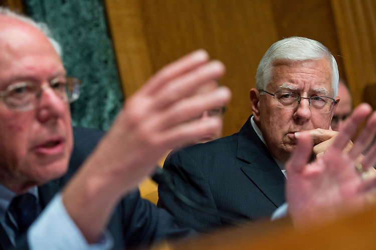 "UNITED STATES - JUNE 17: Sen. Bernie Sanders, I-Vt., left, asks a question as Chairman Mike Enzi, R-Wyo., looks on, during a Senate Budget Committee hearing in Dirksen Building titled ""Congressional Budget Office's Long Term Fiscal Outlook for Nation,"" June 17, 2015. CBO Director Keith Hall testified. (Photo By Tom Williams/CQ Roll Call)"