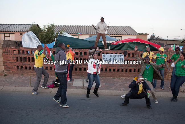 SOWETO, SOUTH AFRICA - JUNE 11: South African soccer fans celebrate a goal by the South African national team on June 11, 2010 in a residential area Soweto, in South South Africa. South Africa played Mexico in the opening game and the final score was 1-1. South Africa didn't advance past the group stage in the 2010 World Cup, held in their own country. In hosting the largest sporting event in the world, South Africa has a chance to impress the world with their country, hoping that the month long event will bring long lasting benefits for the country. (Photo by Per-Anders Pettersson)