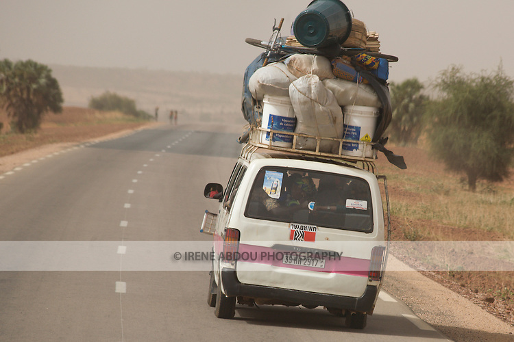 "A ""bush taxi"" travels the two-lane, international highway from Ouagadougou, Burkina Faso to Niamey, Niger.  The taxi will stop anytime on the side of the road to let passengers on and collect new ones.  The 17-seater vehicle can be stuffed with up to 26 people."