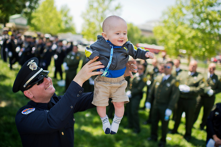 UNITED STATES - MAY 15: Officer David Parks of the Chandler (Ariz.) Police Department, plays with his son William, 6 months, during the 34rd Annual National Peace Officers' Memorial Service on the West Lawn of the Capitol, May 15, 2015, which was part of National Police Week. (Photo By Tom Williams/CQ Roll Call)