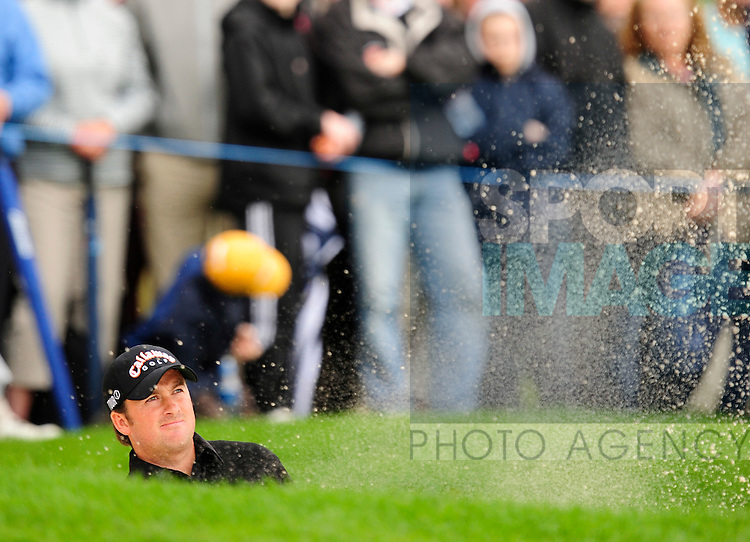 Joint overnight leader Graeme McDowell of Northern Ireland gets himself out of trouble in the bunker on the 17th