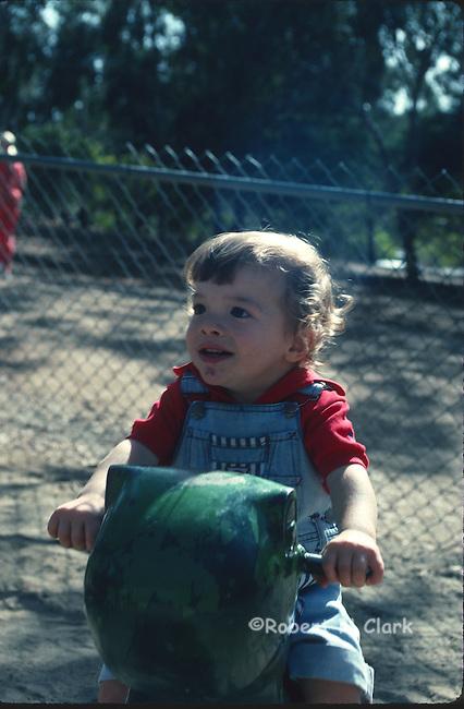 Boy riding toy animal at park